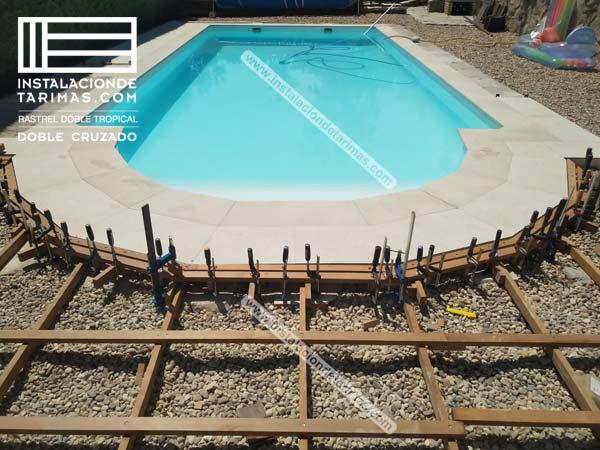 foto de instalación de tarima exterior de ipé con doble rastrel cruzado para continuar una piscina