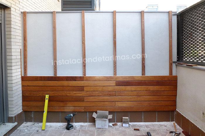 Foto de un muro recubierto con tarima, se ven los rastreles en vertical pegados y atornillados a la pared y la tarima que se empieza a montar desde abajo.