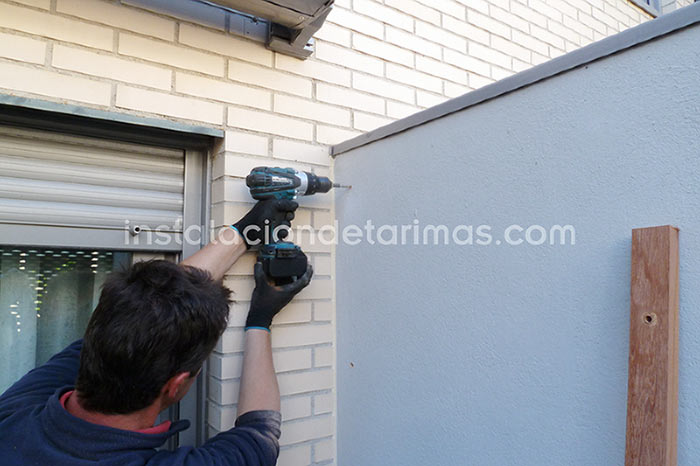 Foto en la que se ve a un instalador taladrando la pared para fijar el rastrel para tener un muro recubierto de tarima
